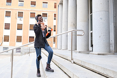 University female african student laughing and speaking on her smartphone, holding a coffee cup on the stairs of the school building on campus. College life concept. - p1166m2236166 by Cavan Images