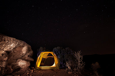 Tent by rock on mountain against starry sky - p1166m969354f by Cavan Images