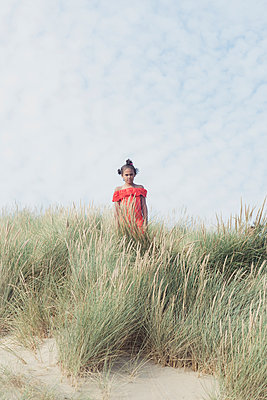 Girl standing in the dunes - p1323m2015156 von Sarah Toure