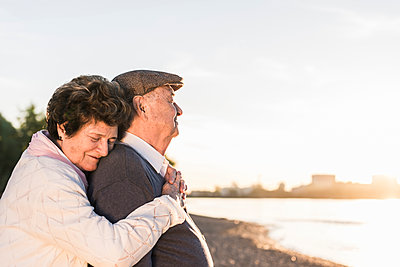 Happy senior couple on the beach at sunset - p300m1459764 by Uwe Umstätter