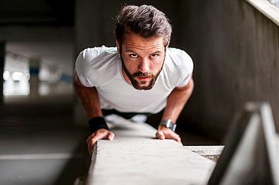 Portrait of man doing push-ups - p300m1587450 von Daniel Ingold