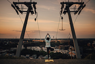 Young female athlete practicing tree pose against sky during sunset - p426m2270538 by Maskot