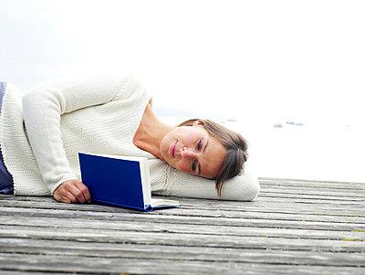 Frau liest Buch auf einem Steg  - p6430085 von senior images