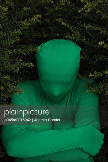 Mensch im Morhpsuit sitzt in der Hecke - p045m2016042 von Jasmin Sander
