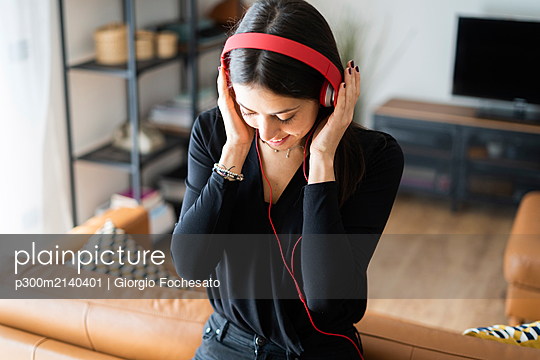 Smiling young woman listening music with headphones at home - p300m2140401 by Giorgio Fochesato