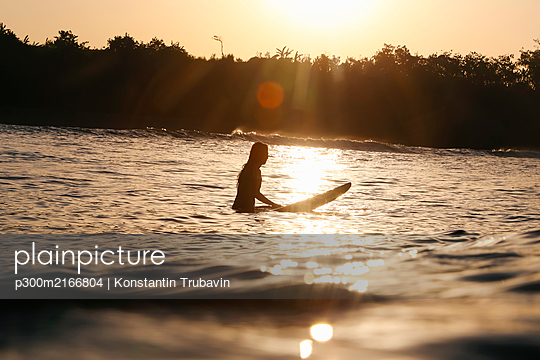 Female surfer at sunset, Bali, Indonesia - p300m2166804 by Konstantin Trubavin