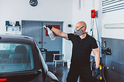 Worker cleaning car while standing in workshop - p1166m2060365 by Cavan Images