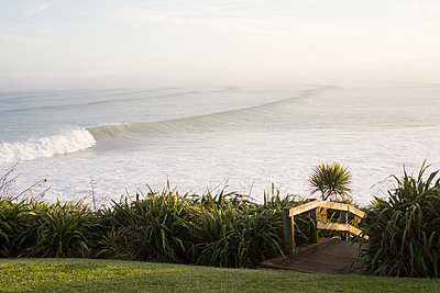 Large surf with morning sea mist and wooden walkway - p1201m1564929 by Paul Abbitt
