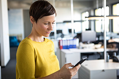 Businesswoman in office looking at cell phone - p300m1205448 by Rainer Berg