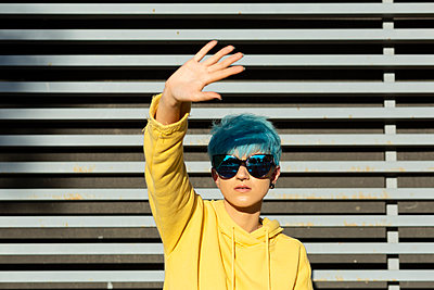 Portrait of young woman with dyed blue hair wearing mirrored sunglasses and yellow hooded jacket - p300m2155718 by Eloisa Ramos