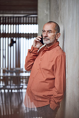 Creative businessman talking on the phone in his minimalistic office - p300m2170496 by Maya Claussen