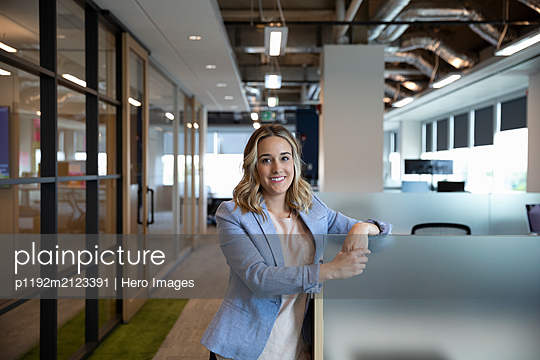 Portrait of young cheerful businesswoman in office - p1192m2123391 by Hero Images