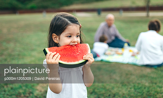 Girl eating watermelon slice with her family in background - p300m1205309 by David Pereiras