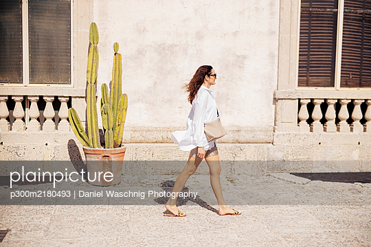 Woman walking along old building, Florida, USA - p300m2180493 by Daniel Waschnig Photography