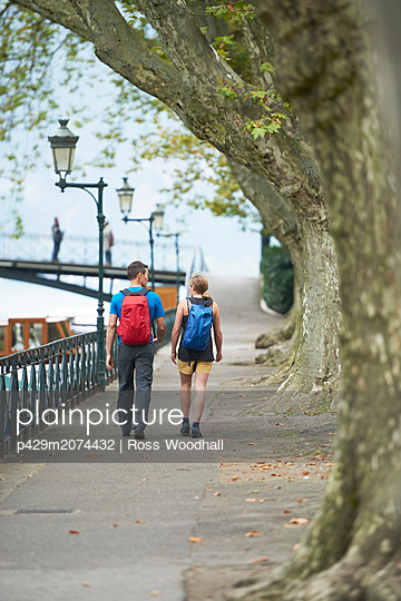 Mature man and young woman strolling along riverside, rear view, Annecy, Rhone-Alpes, France - p429m2074432 by Ross Woodhall