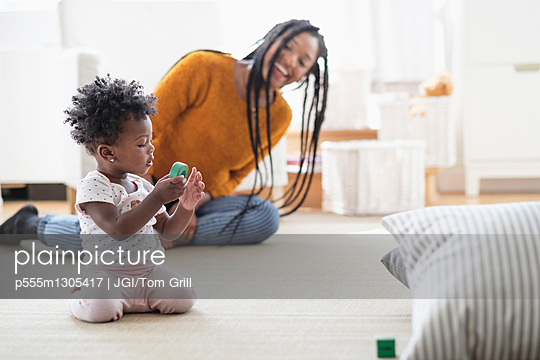 Black woman watching baby daughter play with toy on carpet - p555m1305417 by JGI/Tom Grill