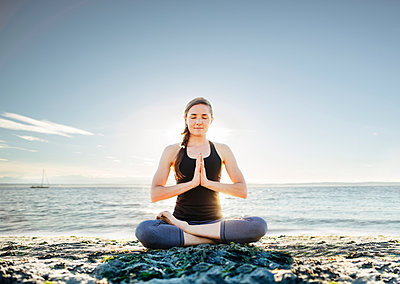 Woman meditating in lotus position at beach against sky - p1166m1227820 by Cavan Images