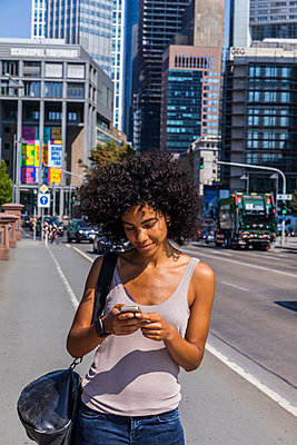 Germany, Frankfurt, smiling young woman with curly hair using cell phone - p300m2030290 by Tom Chance