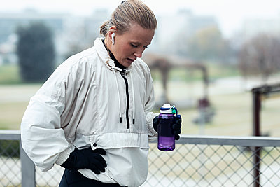 Exhausted female athlete drinking water after exercising in park - p300m2275561 by Josep Suria