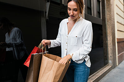 Young woman shopping in streets, Seville, Spain - p300m2300218 von Julio Rodriguez
