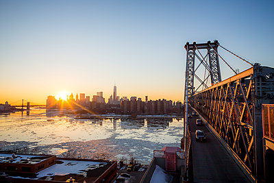 Sunset over a city while on a bridge over a river. - p343m1088992 by Mat Rick