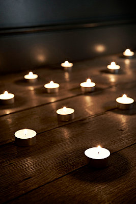 Burning candles on a wooden floor - p3493130 by Jon Day