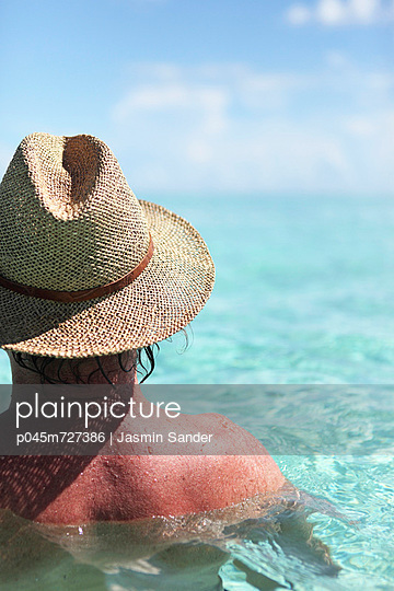 Man with straw hat in the sea - p045m727386 by Jasmin Sander