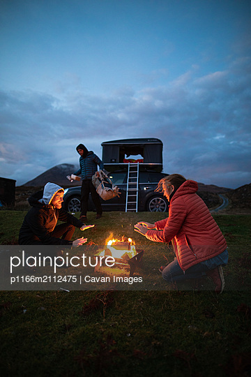 Camping by the fire - p1166m2112475 by Cavan Images