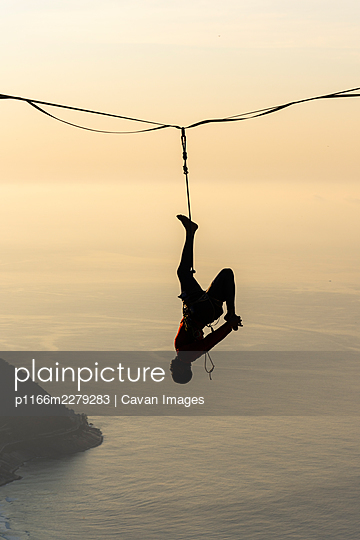 Beautiful view to male highliner silhouette hanging on mountain - p1166m2279283 by Cavan Images