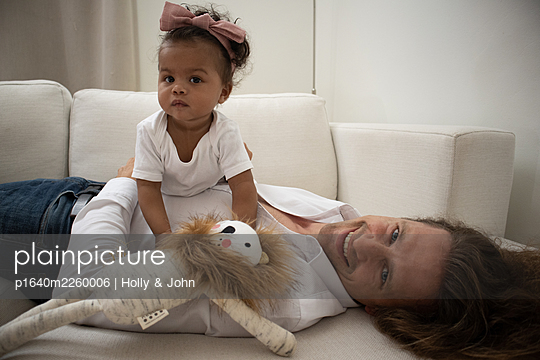 Father and daughter with cuddly toy on the sofa - p1640m2260006 by Holly & John