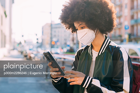 Young multiethnic woman wearing mask using smartphone outdoor - Italy; Lombardy; Milan - p300m2286246 von Eugenio Marongiu