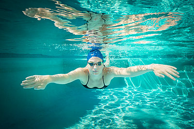 Young female swimmer during training - p1554m2272609 by Tina Gutierrez