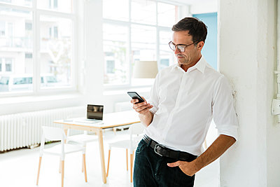 Businessman looking on cell phone in bright office - p300m2062223 by Robijn Page