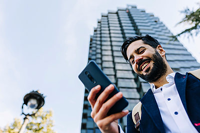 Smiling businessman using smart phone while standing in city - p300m2256887 by Xavier Lorenzo