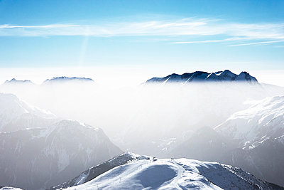 Snow covered mountain landscape with mist,  Alpe-d'Huez, Rhone-Alpes, France - p429m2127696 by Ross Woodhall