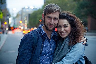 Couple on city street in the evening, portrait - p623m1221425 by Gabriel Sanchez