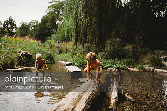 Kids playing in the water in stream by rocks and logs in summer - p1166m2292816 by Cavan Images