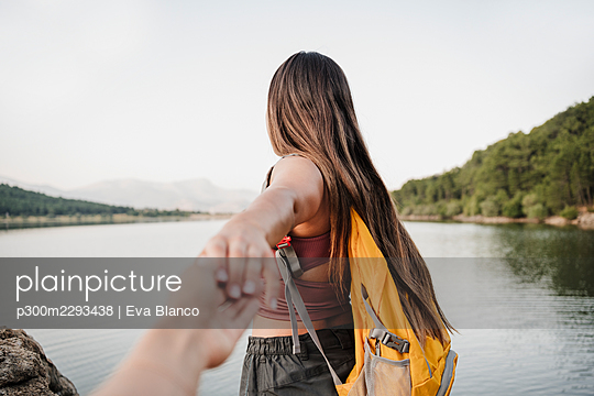 Female backpacker holding hand of friend at lakeshore - p300m2293438 by Eva Blanco