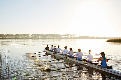 Female rowers rowing scull on sunny lake - p1023m1575837 by Richard Johnson