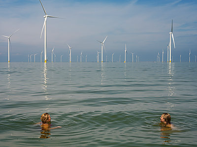 Two women in the sea in the background a wind farm - p1132m2291575 by Mischa Keijser