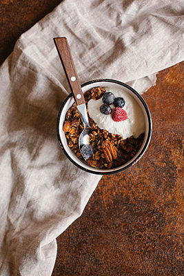 High angle view of granola in bowl on table - p1166m1543251 by Cavan Social