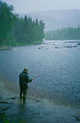 Man fishing in heavy rain - p1418m1571740 by Jan Håkan Dahlström