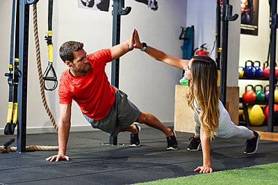 Couple exercising side plank with high-five in a gym - p300m2060294 von Javier Sánchez Mingorance