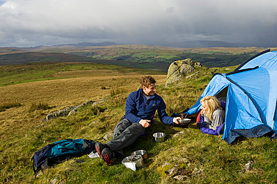 Gilar Farm, Snowdonia, North Wales.  A man and woman camping whilst hill walking in the wilds - p6521508 by John Warburton-Lee