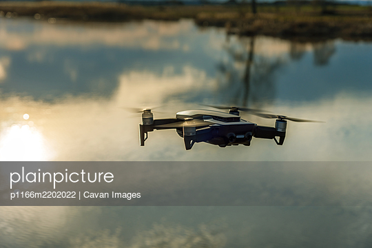 Small modern drone hovering taking picture of sunset. - p1166m2202022 by Cavan Images