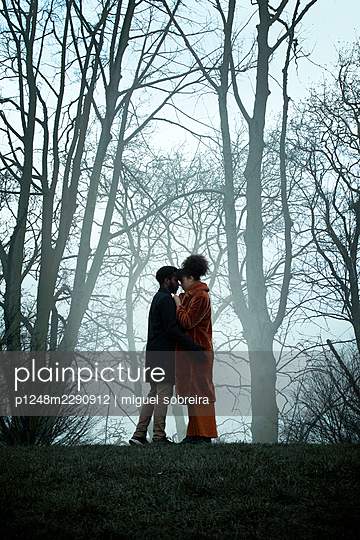 Man And Woman Embracing on Hill By Bare Trees - p1248m2290912 by miguel sobreira