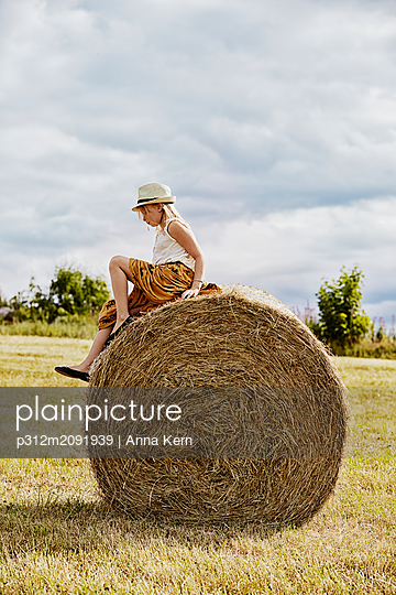 Girl sitting on bale of hay - p312m2091939 by Anna Kern