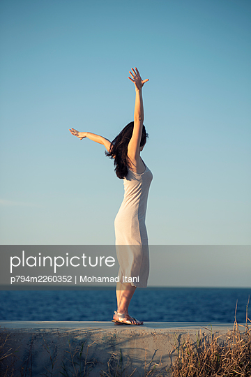 Happy young woman arms outstretched on the beach  - p794m2260352 by Mohamad Itani