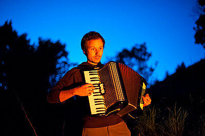 Man playing accordion at night - p1007m854273 by Tilby Vattard