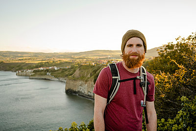 Smiling Bearded man with view of Robins Hood's Bay behind at sun - p1166m2235932 by Cavan Images